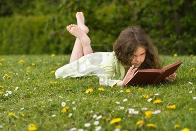 4779296-young-girl-reading-a-book-in-a-grassy-meadow-covered-with-wild-flowers